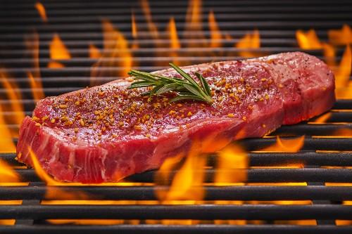 Tri Tip Steak mit Rosmarin und Gewürzen auf dem flammenden Grill