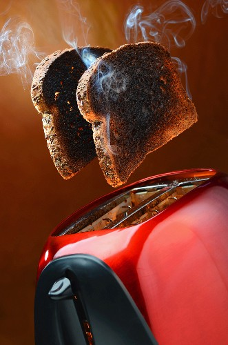 Smoking burnt toast popping out of a red toaster