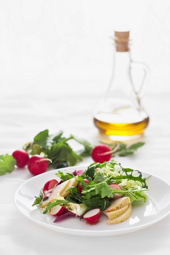 A healthy salad with radishs, pears and olive oil
