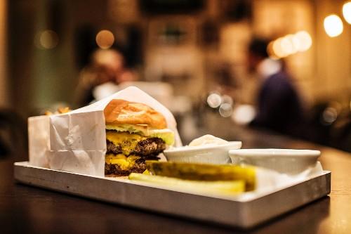 Tablett mit Hamburger, Dips & Essiggurken auf Verkaufstheke