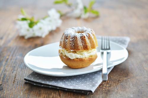 A mini Bundt cake with cream and icing sugar
