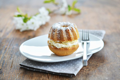 A mini Bundt cake with cream and icing sugar