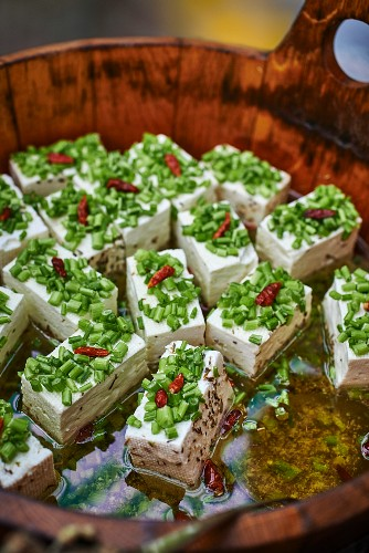 Marinated goat's cheese with olive oil and chives in a wooden barrel