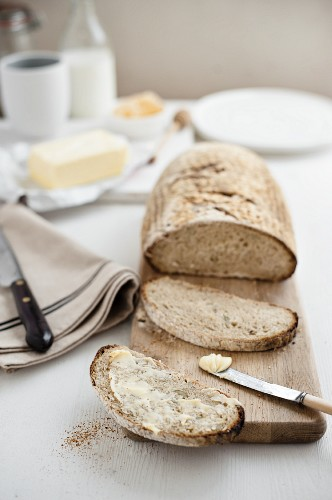 Sauerteigbrot auf Schneidebrett und mit Butter bestrichene Brotscheibe