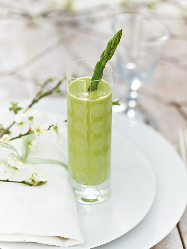 A glass of pea and coconut soup with green asparagus