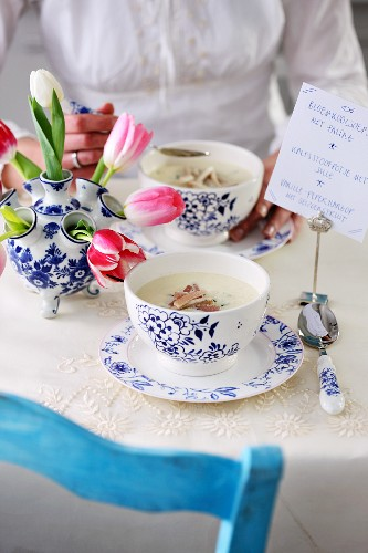 A spring table laid with cauliflower soup, tulips and a menu