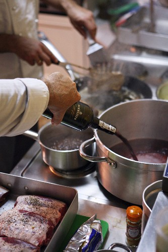A chef preparing meat in a kitchen