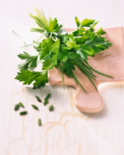 Parsley and chives on a chopping board
