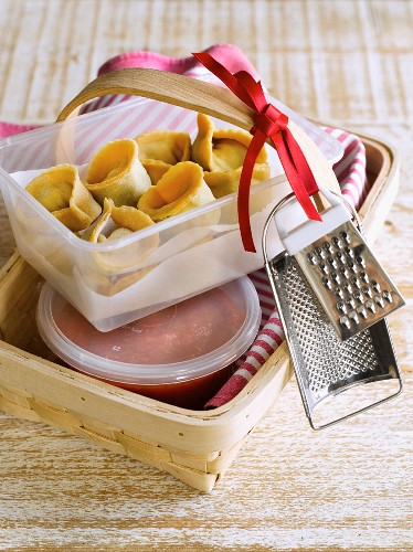 Homemade pasta parcels with tomato sauce as a gift in a wooden basket