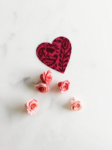 A paper heart and pink marzipan roses as cake decoration