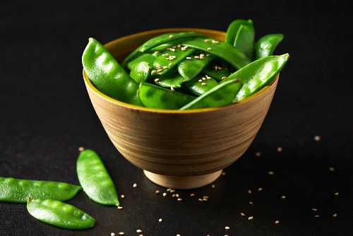 Mange tout with sesame seeds in a wooden bowl (Paleo diet)
