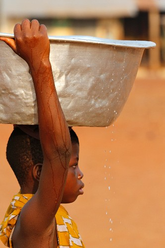 A child carrying a bowl of water on his head in an African village, Togo, West Africa