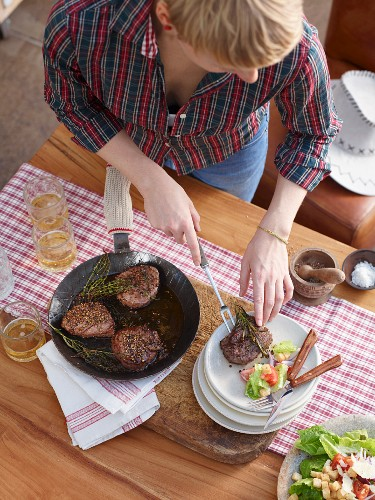 A woman arranging pepper fillet steaks on plates