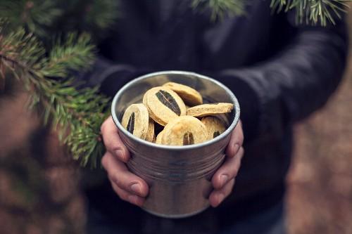 A man holding a metal bucket of green tea cookies