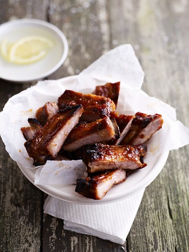 Marinated spare ribs in a bowl lined with a piece of paper