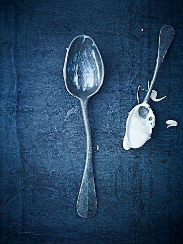 Two antique spoons with cream on them, one bent (seen from above)