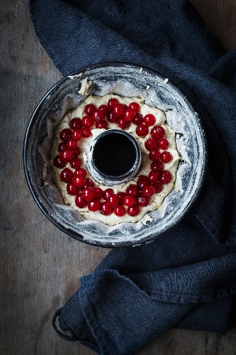 Cake mixture with redcurrants in a Bundt cake tin on a dark wooden surface with a grey cloth