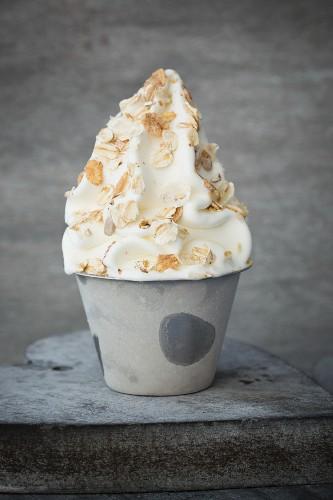 Frozen yoghurt in a metal cup with muesli