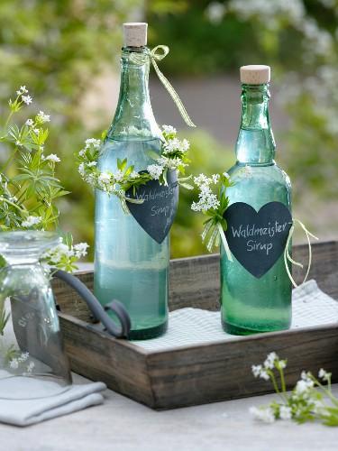 Selbstgemachter Waldmeistersirup als Geschenk mit Herzen und Kränzchen um Flaschenhals