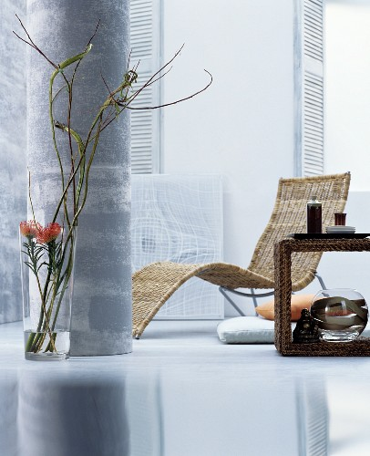 An oriental style living room with a lounger, a side table and decorative plants in a floor vase by a pillar