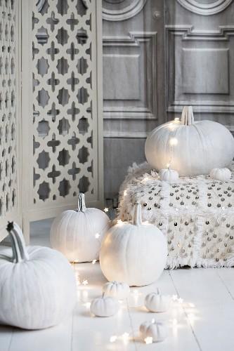 Halloween arrangement of white-painted pumpkins, fairy lights and floor cushions