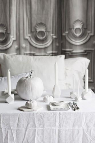 Dekorierter Halloween-Tisch mit Kürbissen und Kerzen in Weiss