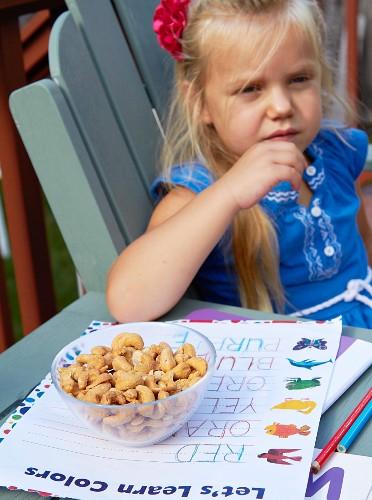 Kleines Schulmädchen isst Cashewkerne