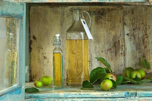 Two bottles of apple vinegar with paper labels and apples in a rustic cupboard niche