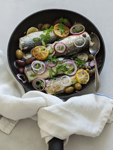 Fried fish in a pan with olives, capers, onions and lemons