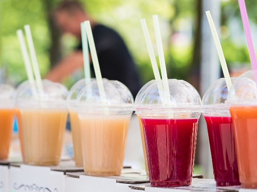 Various juices in plastic cups at a market stall