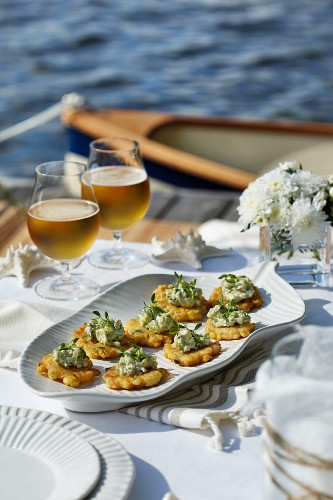 A table by the water laid with corn fritters and beer