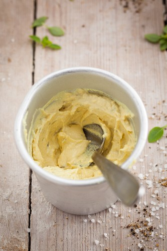 A bowl of mustard with a spoon
