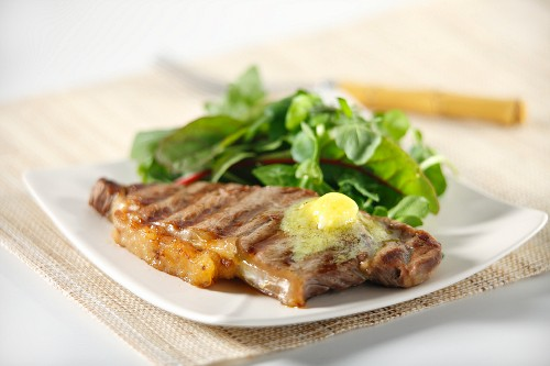 A grilled steak with garlic butter