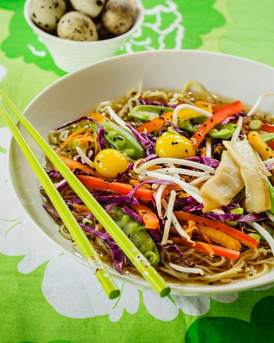 Stock with ramen noodles, colourful vegetables and quail's eggs (Asia)