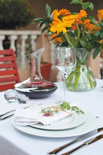 Weiss gedeckter Tisch mit Rotweinkaraffe und orangefarbenem Blumenstrauss