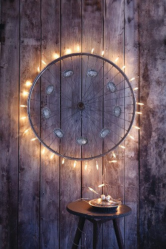 An old bicycle wheel upcycled with fairy lights to make a Christmas decoration