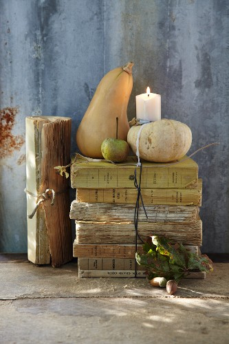 An autumnal arrangement of antique books, ornamental pumpkins and a candle