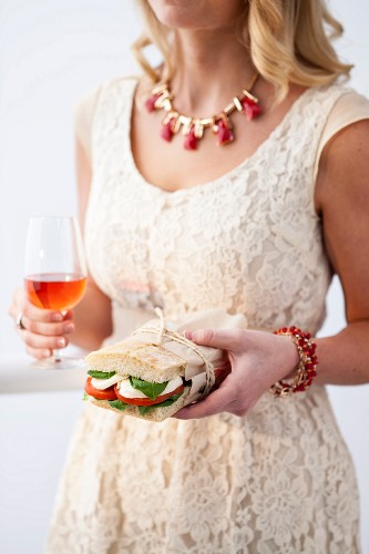 A young woman with a tomato and mozzarella sandwich and an aperitif