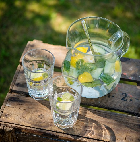 Lemon water with cucumber and mint on a wooden crate in the garden