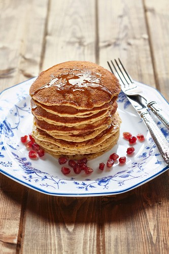 A stack of pancakes with honey and pomegranate seeds