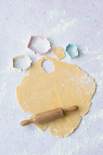 Rolled out shortcrust pastry with baking utensils for making children's biscuits