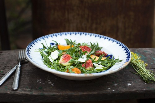 Rocket salad with figs, plums and sheep's cheese on a wooden bench outside