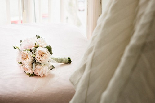 A bridal bouquet on a bed next to a hanging wedding dress