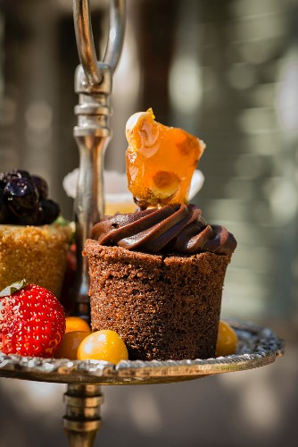 A small chocolate cake and fruits on an étagère