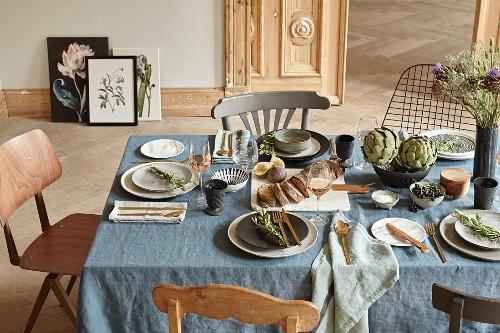 In provenzalischem Stil gedeckter Tisch mit blauer Leinentischdecke und duftenden Dekorationen