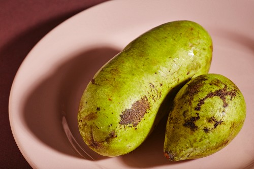 Two ripe pawpaws on a pink plate
