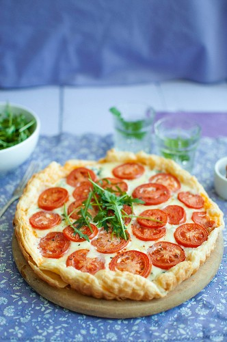 Puff pastry tart with red pestol, blue cheese, mozzarella, tomatoes and rocket