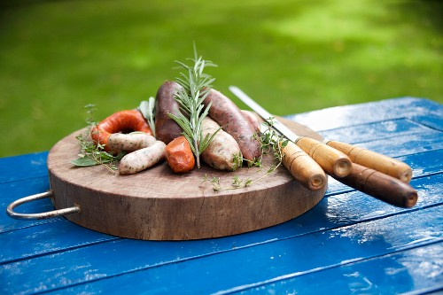 A wooden platter with various uncooked sausages, herbs and skewers
