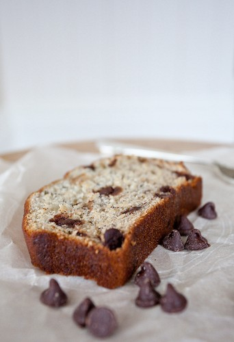 A slice of banana bread with chocolate chips on a piece of parchment paper