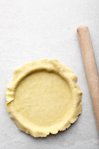 A tart being made: pastry being placed in a tart tin